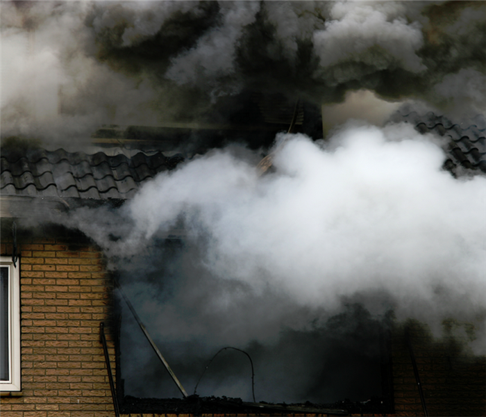 smoke billowing from the windows of a building