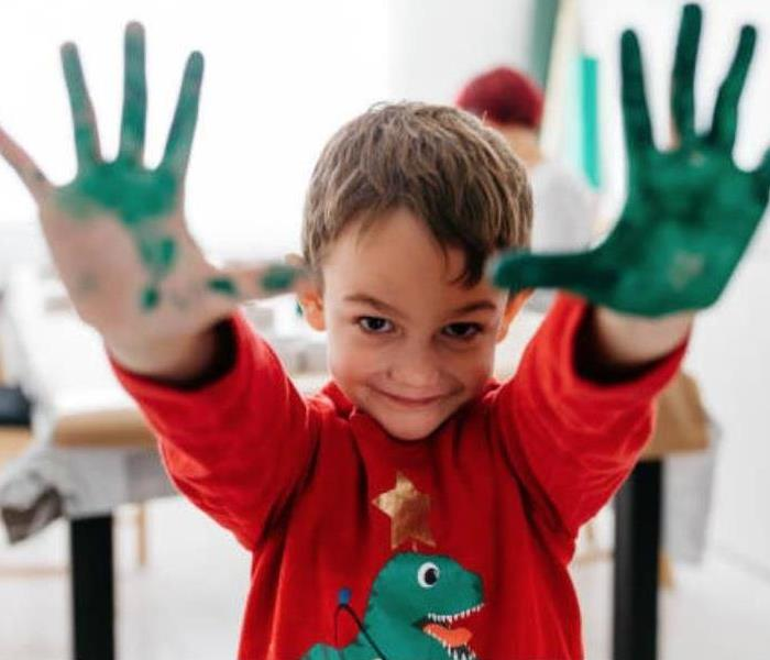 A child with green paint all over him.