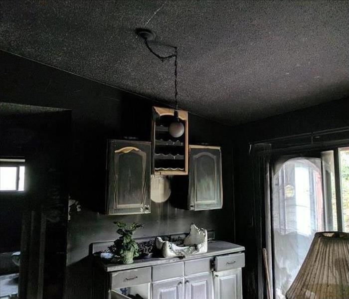 A kitchen covered in soot and smoke damage after a fire disaster